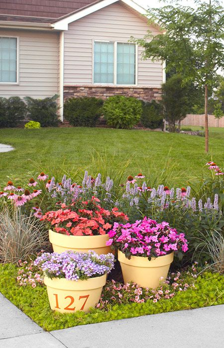 Put a colorful garden to work in your front yard. Bright flower pots prominently display house numbers.