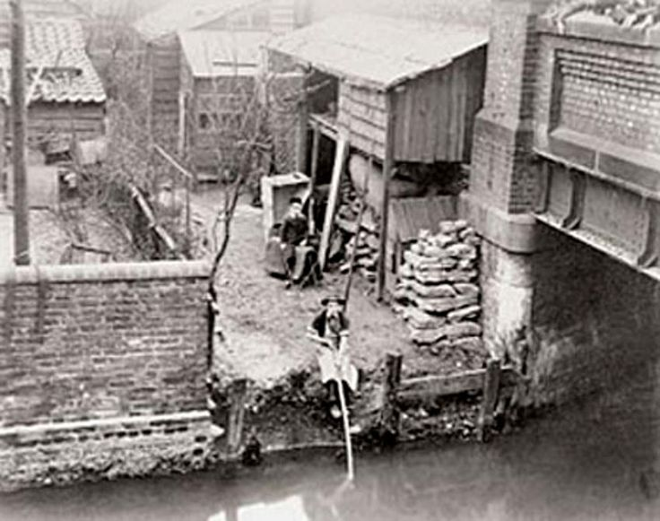 Somewhere on the Bow Back Waters around 1900. It was originally called Stratford Marsh... By the eighteenth century industrialisation was taking place and many wharfs were created to accommodate the import of timber, chalk, stone, coal, and wheat. By 1821, the earliest proper dock named Stratford Dock, later called Meggs Dock was created just up from Bow Bridge but after 1920, the whole site had been filled in and was occupied by factories and workshops that didn't depend on water access.