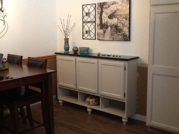 We took an old upper cabinet from our laundry room and turned it into a buffet for our dining area.  My husband added the cubbies on the bottom, we had it sprayed to match our newly painted kitchen cabinets, attached it directly to the wall, added bun feet to the front and had a scrap piece of granite cut to fit the top.