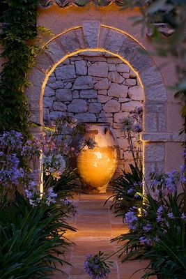 MEDITTERANEAN STYLE GARDEN - VIEW ALONG BRICK PATH TO FOCAL POINT TERRACOTTA CONTAINER, ARCH AND AGAPANTHUS