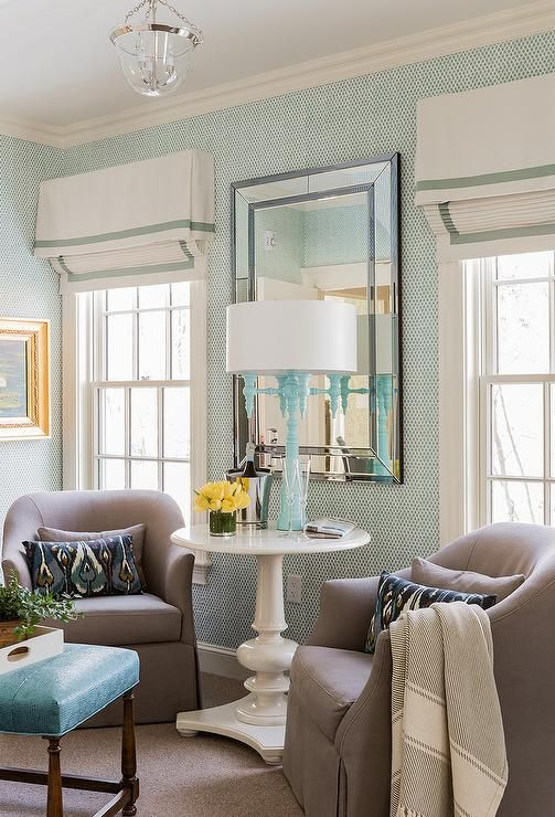 You'll feel right at home in this appealing transitional living room featuring a beveled mirror mounted between windows dressed in white and blue pleated valances and framed by blue print wallpaper.