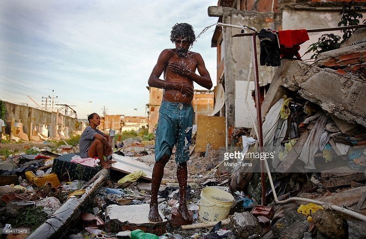 A man bathes from a small hose amongst the remains of demolished homes in the Metro Mangueira favela, located near Maracana stadium, on May 22, 2014 in Rio de Janeiro, Brazil. The homes were thought to have been knocked down for a parking lot for the stadium, though that has yet to be built. The area has seen some people occupy certain dwellings. Evictions and demolitions have been occurring in Rio favelas ahead of the 2014 FIFA World Cup and Rio 2016 Olympic Games in spite of a housing…