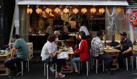 "Visitors eat at an ""izakaya"" (Japanese pub - 居酒屋) in Tokyo."