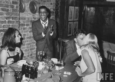 1963: Elizabeth Taylor (L) and Sammy Davis Jr. (2L) look on as Richard Burton (2R), gives a friendly buss to Sammy's wife May Britt.