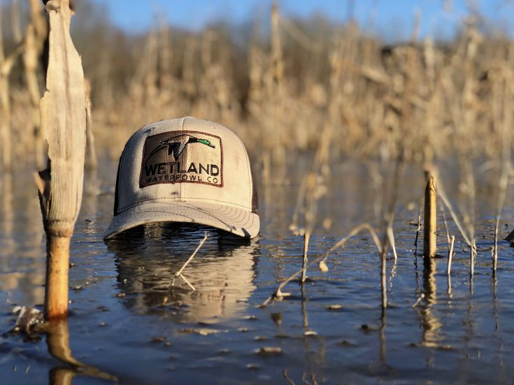 A WWC hat over an icy pond makes for a perfect day of duck hunting. Get your hat now at wetlandwaterfowlcompany.com.