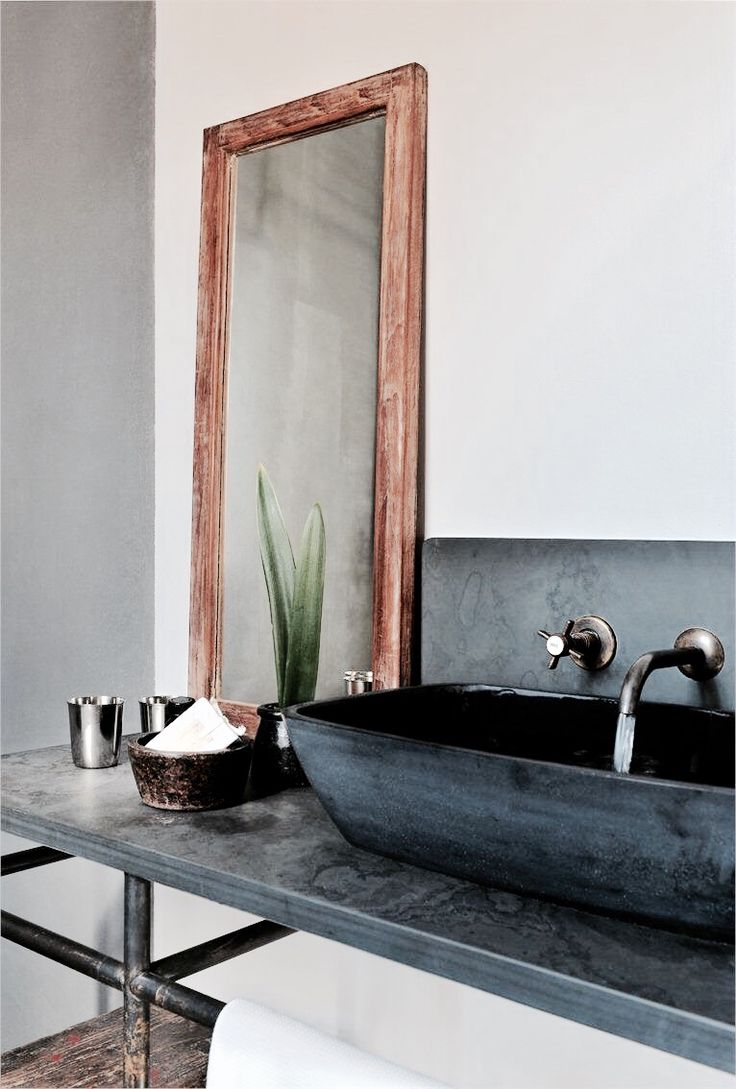 rustic | masculine | earthy | texture | raw metal | black sink basin | wall mounted faucet | rough wooden mirror | open framed vanity