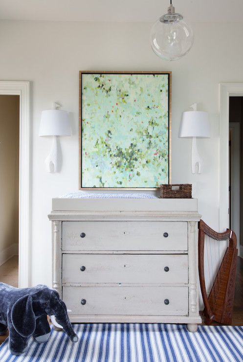 Adorable boy's nursery boasts mint green abstract art illuminated by Jonathan Adler Giraffe Wall Sconces over a distressed changing table with three drawers flanked by doorways alongside a kid sized harp and velvet elephant atop white and blue stripe rug, Dash & Albert Lighthouse Denim/White Indoor/Outdoor Rug.