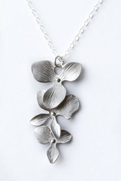This beautiful sterling silver necklace with white gold plated orchids dangling vertical is stunning on!    Total length is 16″    Matching bracelet and earrings are available. $59