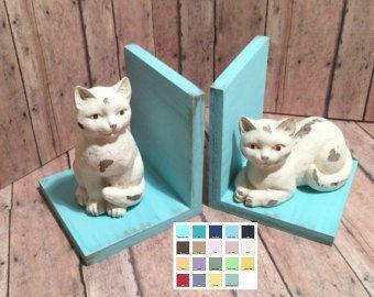 """Cat Set of Bookends Available Каждый форзац примерно 4 3/4 """"высотой х 4 1/4"""" глубокий х 4 1/4 """"широкий Сидящая кошка 5."""" Высокий; лежащий кошка 3 1/4 """"в высоту и 4"""" долго. Каждый заказ включает в себя набор (левый и правый). В форзацы сделаны из исправленного леса, окрашенная ваш выбор цвета, проблемного и скрепленного печатью. Цвета показано: яйцо малиновки голубой, светло-зеленый шалфей, темно-синий и зеленовато-голубой."""