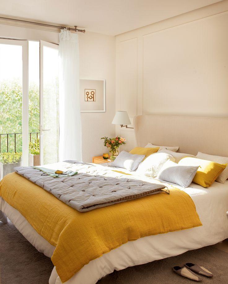 dormitorio principal con cabecero tapizado alfombra y ropa de cama en gris y amarillo