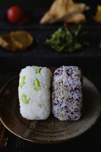 枝豆の翠色、紫蘇の紫色が美しい「おにぎり」2種。  白いご飯に具材を混ぜ込んだり、炊き込みご飯を結んだり、具材を芯にして握ったり、サンドイッチのように挟んだりと、おにぎりのバリエーションは実豊富。
