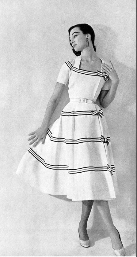 1954 Ivy Nicholson in white toile dress decorated with royal blue and white striped gros-grain ribbons, from Pierre Balmain
