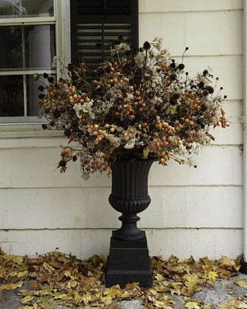 Dried, dead, or dark flowers and a black metal/plastic pot for outdoor Halloween decorating.