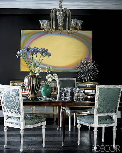 Decorator Nate Berkus mixes abstract art with classic old-world furnishings in the dark, black dining room of a Chicago apartment. The dark Louis XV–style table is by Dessin Fournir, the vibrant painting is by Dan Christensen and the vintage steel sculpture is from Pavilion Antiques.