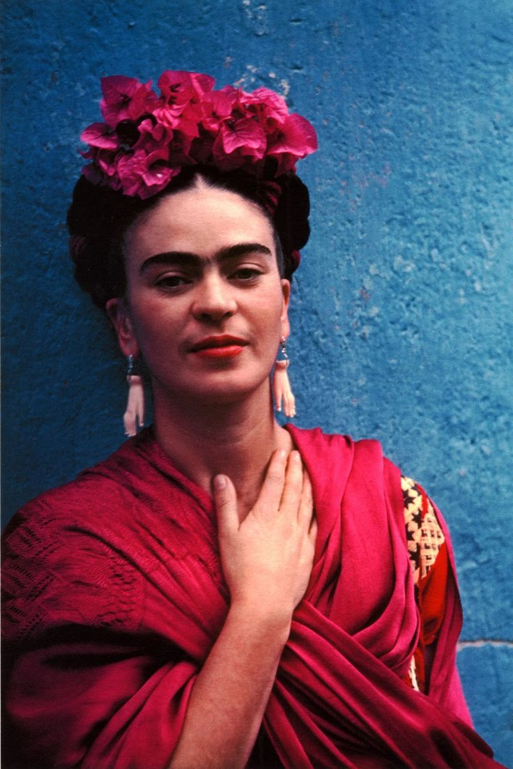 Frida Kahlo in 1939. I love that she's wearing bougainvillea in her hair, and that her earrings are hands.