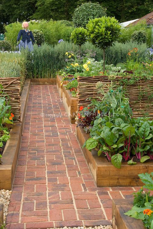 Vegetable garden with brick pathway and girl scarecrow. Love the look of garden and no mowing or weeding between plots!