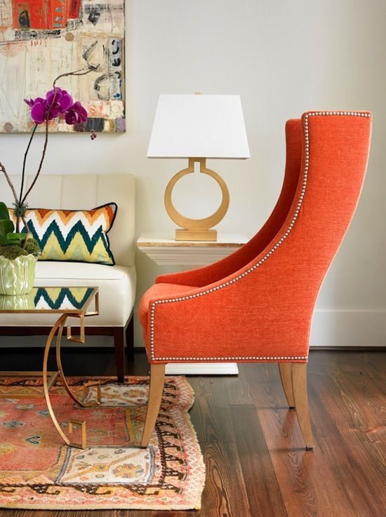 orange studded modern wingback with brass coffee table
