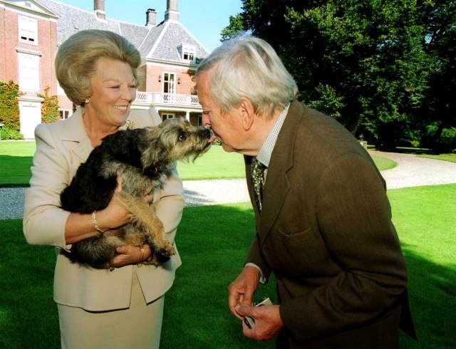 Queen Beatrix of the Netherlands with her dog Dushi giving Prince Claus a kiss