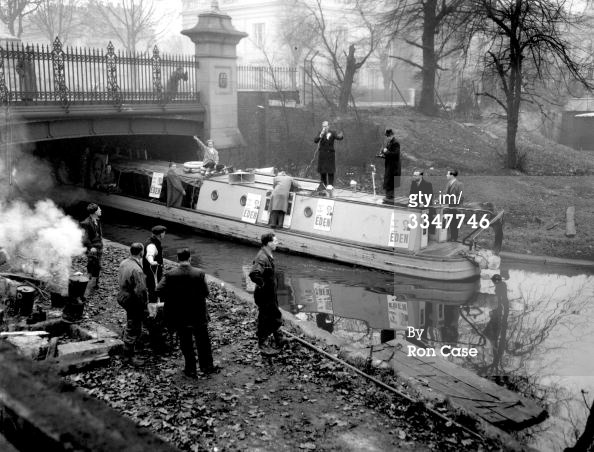 "Captioned: ""1st December 1953: John Eden, the Tory candidate for North Paddington, electioneering by barge along the Grand Union Canal. Workmen on the bank watch the barge go by as John Eden speaks through a microphone on board."" #london #canal #barge #narrowboat #paddington #little #venice #workmen #john #eden #regents #grand #union #politician"