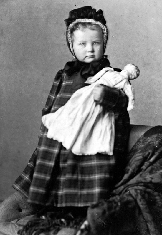 Wee girl in her tartan coat with a doll