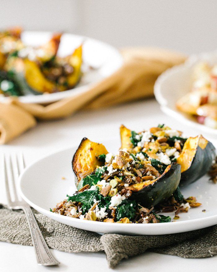 Roasted Acorn Squash with Wild Rice Pistachio Stuffing | a Couple Cooks (easily omit cheese for vegan)