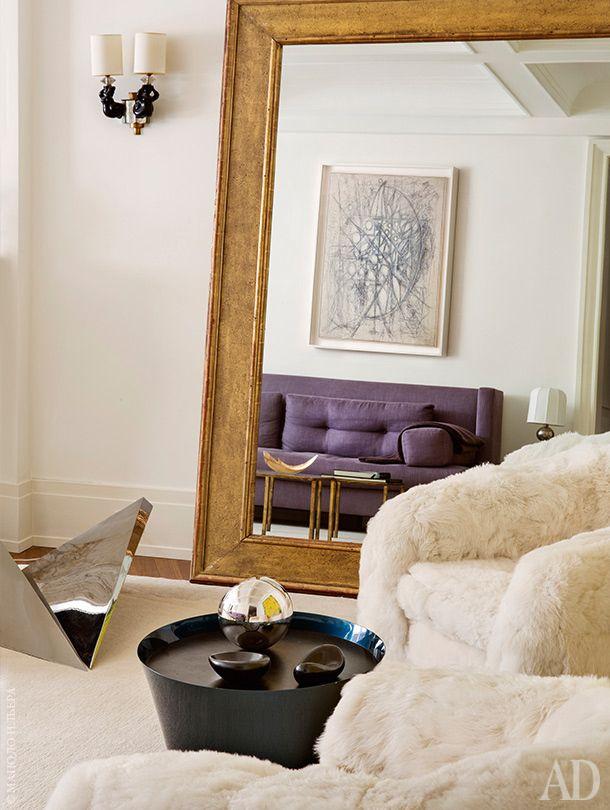 Фрагмент гостиной. В зеркале отражается диван, сделанный по эскизам хозяйки квартиры. Металлическая скульптура на полу — работа Беверли Пеппер. Журнальный столик — по дизайну братьев Буруллеков.
