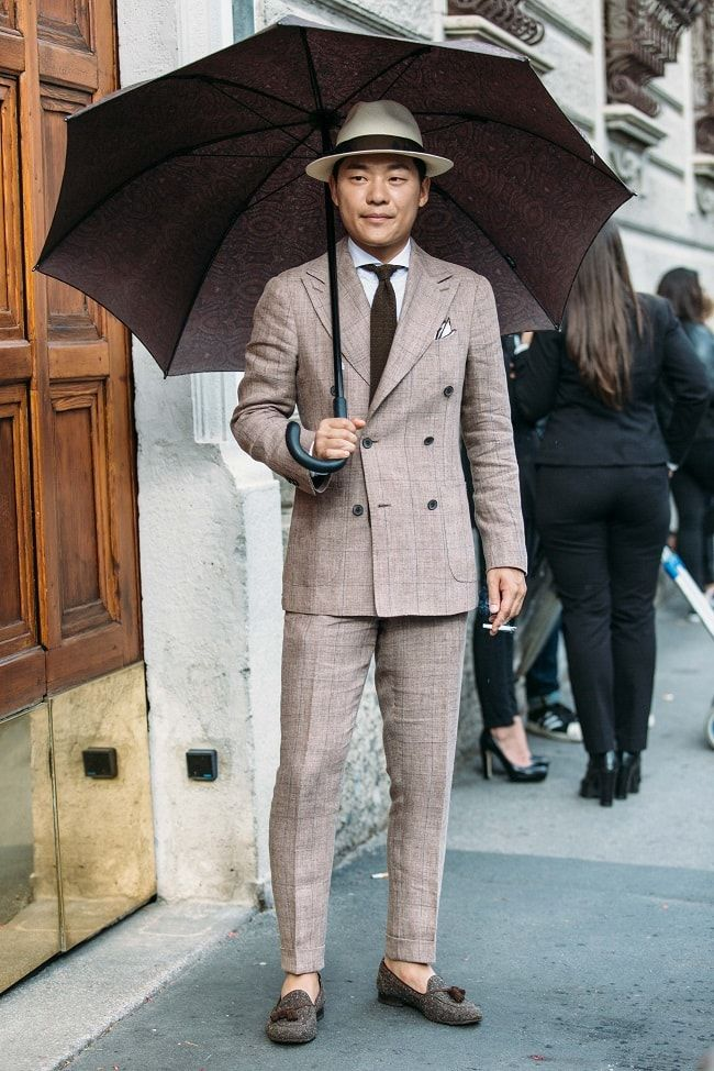 A young dapper dandy wearing exquisite summer suiting on the street of Milan in…
