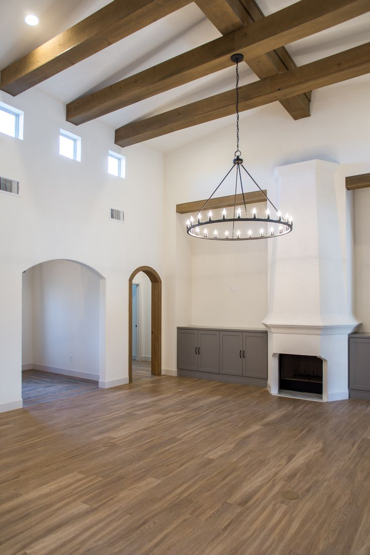 mediterranean style living area with tall ceilings stained beams and decorative fireplace by - Ubahnaufkantung Grau