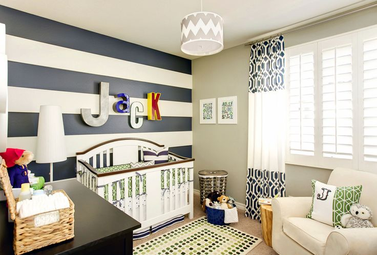 This striped accent wall gives this nursery a punch of bold color!