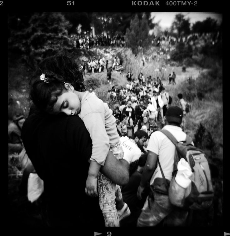 A refugee carries his daughter as he and others make their way to the Greece-Macedonia border – Idomeni, Greece, August 2015 [Giorgos Moutafis]