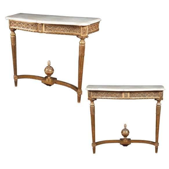 Par de aparadores estilo Louis XV, de madeira entalhada e dourada, tampo de mármore recortado, duas pernas dianteiras amarradas entre si por travessa encimada por globo e pinha.<br>110 x 44 x 93 cm de altura.<br>França, séc. XIX.