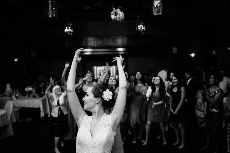 bride throws bouquet in black and white