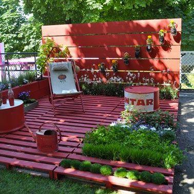 Sol terrasse dans jardin fabriqué avec des palettes en bois puis peintes en rose intense. Claustra bois et jardinière assorties