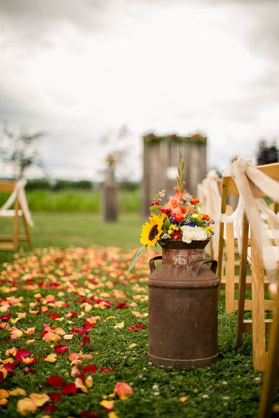 Wildflowers in vintage milk cans as rustic wedding ceremony decor {Genesa Richards Photography}