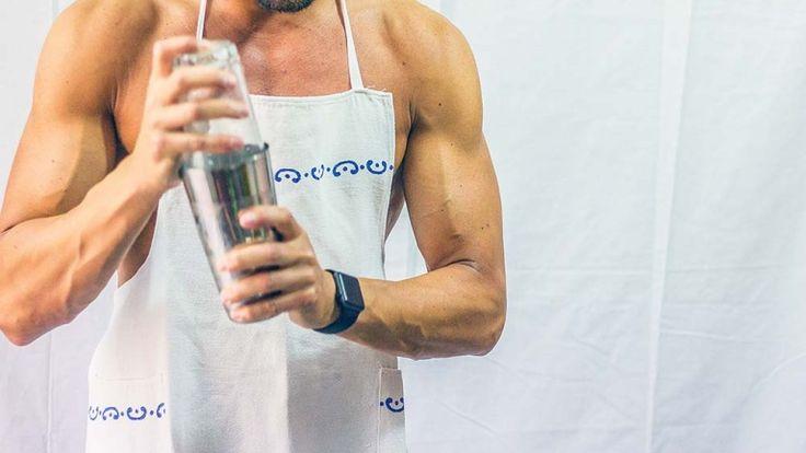 Modello muscoloso nudo in cucina con shaker in mano e bicipiti erculei