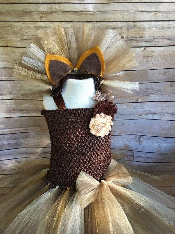 Uw kleine dame ziet er absoluut schattig in deze Leeuw kostuum tutu jurk met bijpassende hoofdband met oren. Een perfect cadeau voor het meisje, die houdt van spelen jurk omhoog, voor een halloweenfeest truc of behandelen, fotoshoot, vakantie-evenement of gewoon spelen jurk omhoog!  * Aanbieding is voor hoofdband en kleding alleen.  Deze bruin, goud en bruin kostuum Leeuw functies 2 volledige lagen van tulle gekoppeld aan een rekbare Gehaakt topje met lint bandjes en een staart garen…