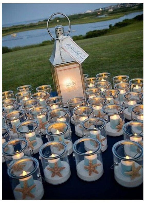 Pièce maîtresse de mariage au bord du lac avec des bougies et une étoile de mer