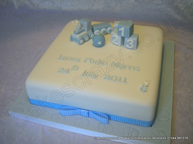 White square celebration christening cake with hand made sugar toys featuring a train, ball, and building blocks. Finished with a blue gingham ribbon and feet embossed cake board