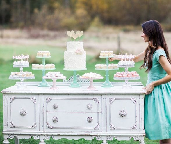 This country chic dessert table displays a white two-tiered cake, cupcakes, cake pops and macarons on pastel colored cake stands.