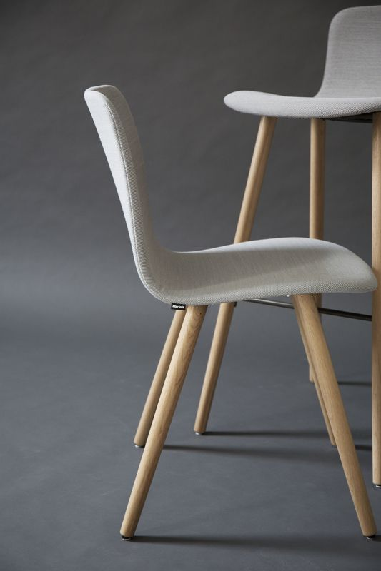 The wooden legs of Sola chair create a warm and cozy feeling. The chair is available with several upholstery options. Design Antti Kotilainen