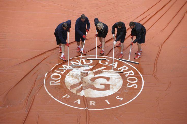 01.06 Les bénévoles de Roland Garros s'activent pour dégager la pluie accumulée sur les bâches.Photo: Kenzo Tribouillard