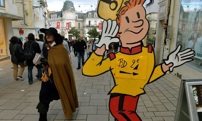A man in a caped costume walks past a sign advertising comics for sale at the Angoulême festival this weekend. #France #Angouleme #festival #comics #best #books #creators #fun #ceremony #artists