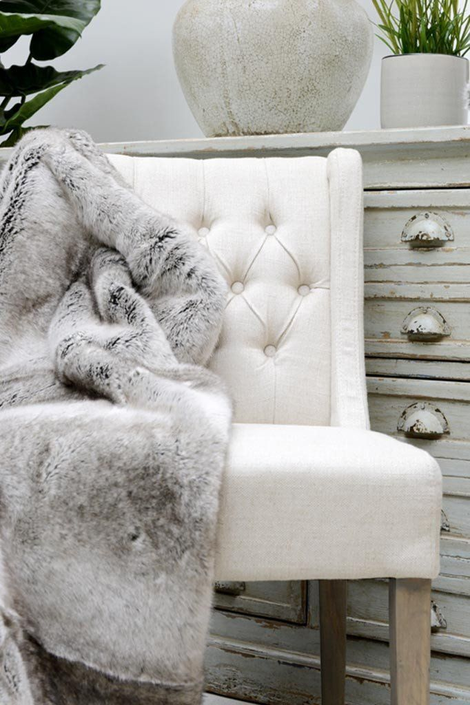 Shadow faux fur throw dropped over a white dining chair