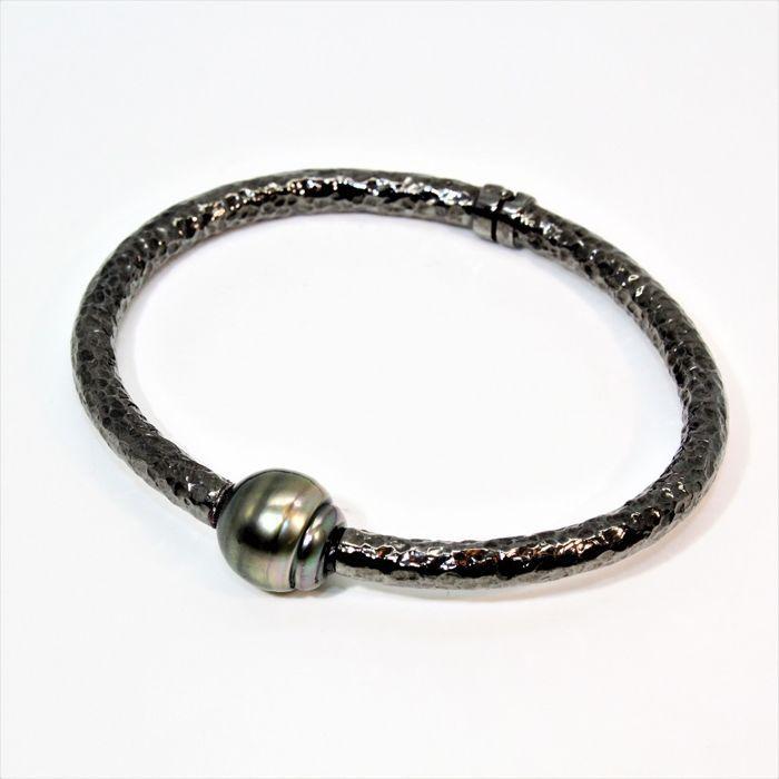 Stijve armband in gehamerd zwarte rhodium-plated 925 zilver en barokke Tahitian parel van Ø 12-13 mm  Rigid gehamerd zwarte rhodium-plated 925 zilveren armband met opening scharnier en gekweekte BQ Tahitian parel Ø 12-13 mm.Oorsprong van de parel: Frans-PolynesiëMetingen van de parel: Ø 12-13 mmVorm: barokNatuurlijke zwarte kleur met donkere tinten van groen en aubergine.Kwaliteit: B/AAAOppervlakte: schoon met lichte onvolkomenhedenUitstekende lustre.Producerende oester: Pinctada…