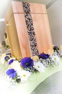 Holz-Urne mit Kieseln auf kleiner Blumenwiese. Aus dem Sortiment von Bestattungen Masermann-Neumann, ausgestellt und gestaltet von Blumen Buchalik in Essen-Steele.