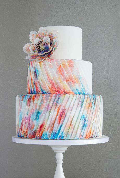 Brides: A Three-Tiered Tie-Dye Pleated Cake. Melonie Stanger of For Goodness Cakes took cues from the fashion runways when creating this watercolor wedding cake. The precise fondant pleats on the bottom tiers convey a sense of movement, and the soft, watercolor hues are hand-painted in pretty shades of pink and blue.