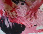 Mixing red and white for finger painting on hearts.
