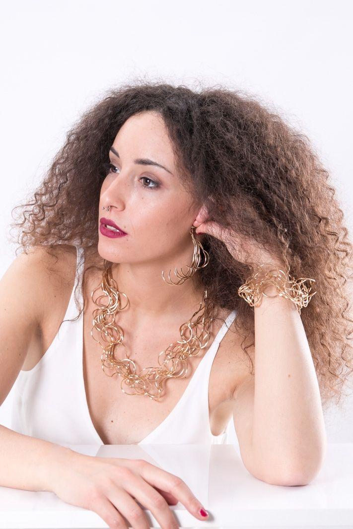 Parure in metallo dorato composta da collana, bracciale e orecchini pendenti. Sono tutti realizzati da un intreccio metallico in oro lucido.Orecchini con chiusura a clip. Bracciale e collana con chiusura classica a moschettone. Elegante e raffinata, perfetta per l' estate fa risaltare l' abbronzatura della pelle. Da abbinare con un total look per un risultato chic.  #paure #DANI #accessori #eleganza #moda #donna