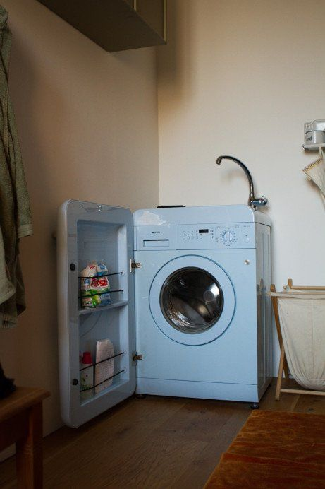 blue smeg washing machine open - storage for detergent built in.  sink on top for removing stains and hand washing.