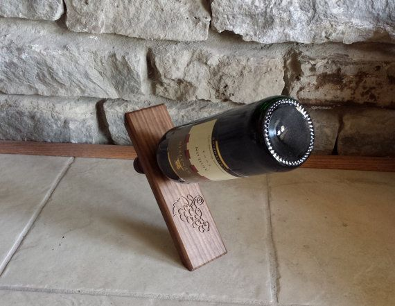 Custom Wine Bottle Holder has grapes engraved on the front. This Wine Bottle holder defies gravity!  Made from walnut and finished with a coat